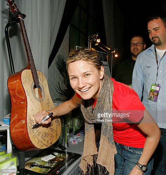 Singer/songwriter Jennifer Nettles autographs a guitar at the Ear Foundation/Clarity display in the Distinctive Assets gift lounge during the Academy...