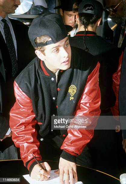 Singersongwriter Joey McIntyre of New Kids On The Block signing a legal document circa 1990