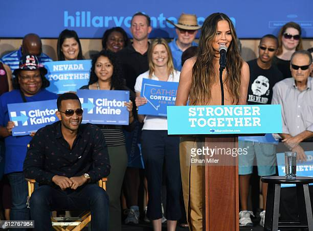 Singer/songwriter John Legend sits onstage as he listens to his wife model and television personality Chrissy Teigen speak at a campaign event with...