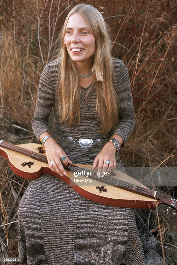 Singer-songwriter Joni Mitchell sitting in a meadow with a mountain dulcimer at her Laurel Canyon home. Mitchell remains one of the most acclaimed songwriters and performers of rock music since the sixties.