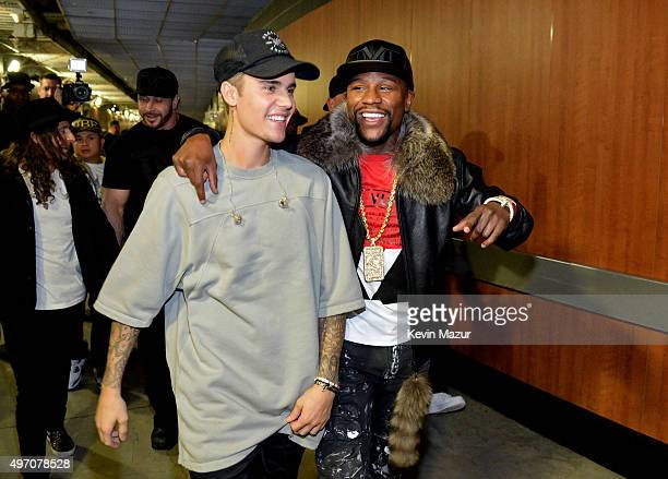 Singer/songwriter Justin Bieber and professional boxer Floyd Mayweather Jr walk backstage during an evening with Justin Bieber to celebrate the...