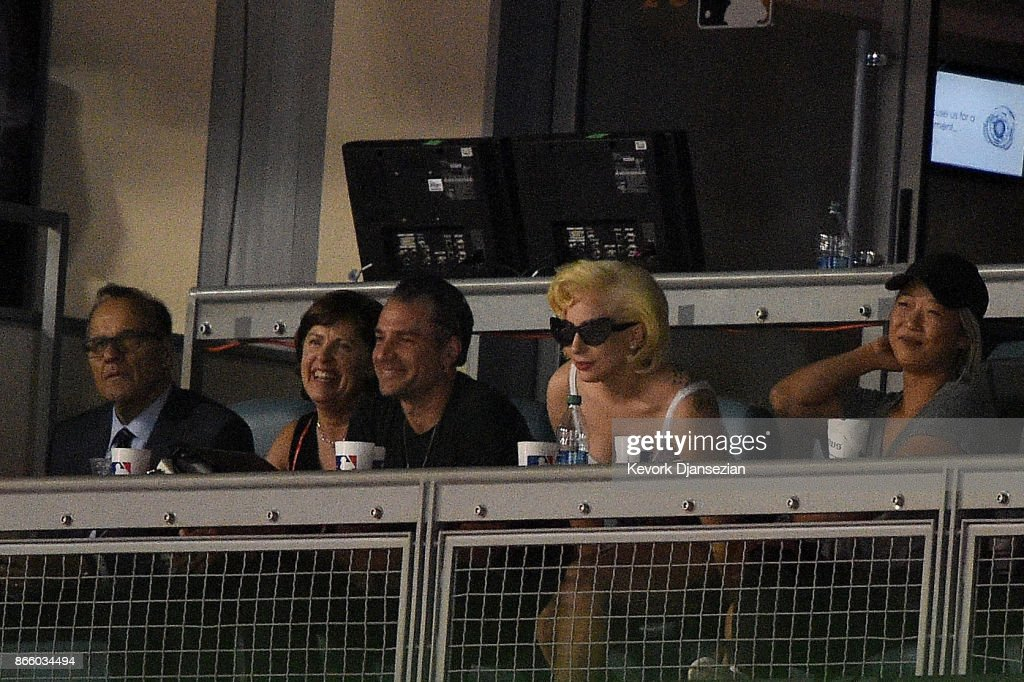 Singer-songwriter Lady Gaga (C) and MLB chief baseball officer Joe Torre (L) attend game one of the 2017 World Series between the Houston Astros and the Los Angeles Dodgers at Dodger Stadium on October 24, 2017 in Los Angeles, California.