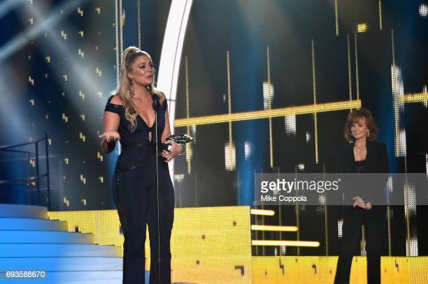 Singersongwriter Lauren Alaina accepts an award onstage from Reba McEntire during the 2017 CMT Music Awards at the Music City Center on June 6 2017...