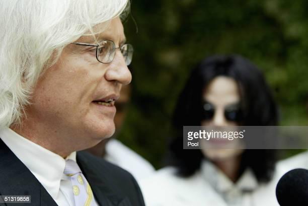 Singer/songwriter Michael Jackson listens as his attorney Thomas Mesereau Jr speaks to the press outside the Santa Maria courthouse on September 17...