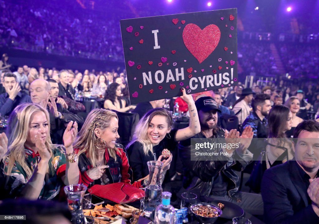 Singer-songwriter Miley Cyrus (C) holds a sign reading 'I heart Noah Cyrus' while she and Tish Cyrus (2nd from L) and singer-songwriter Billy Ray Cyrus (R) attend the 2017 iHeartRadio Music Awards which broadcast live on Turner's TBS, TNT, and truTV at The Forum on March 5, 2017 in Inglewood, California.