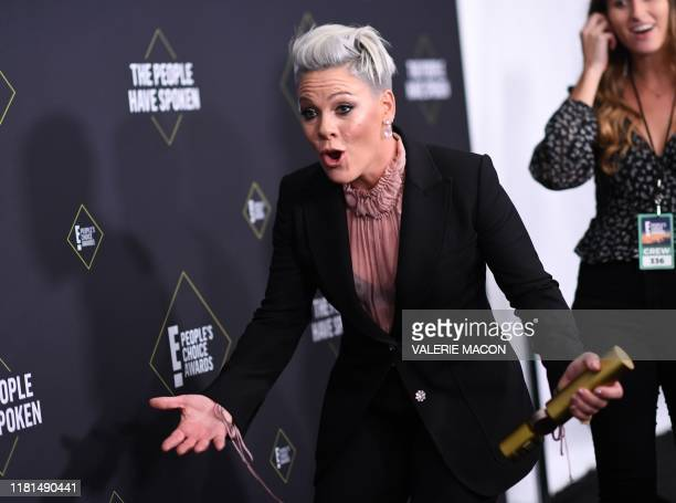 US singer/songwriter Pink reacts as her son Jameson Moon Hart runs towards her as she gets ready to pose with the Peoples Champion Award during the...