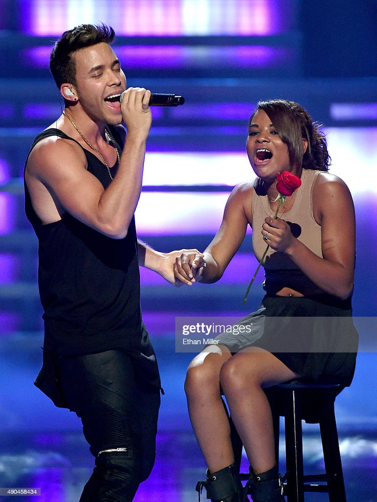 Singer/songwriter Prince Royce (L) sings to a fan as he performs at the 2015 iHeartRadio Music Festival at MGM Grand Garden Arena on September 19, 2015 in Las Vegas, Nevada.