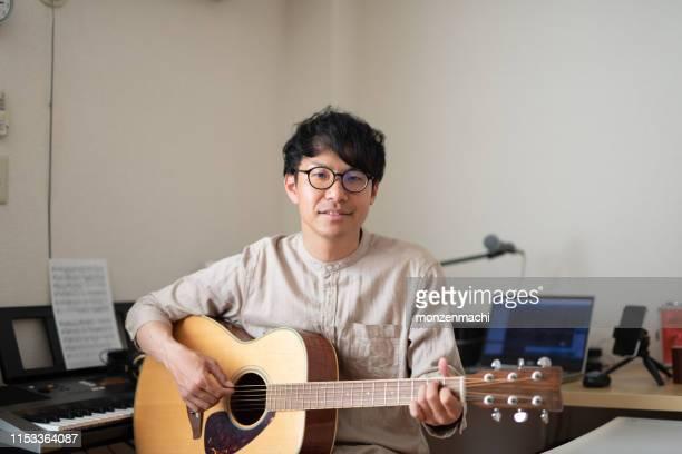 ルームでギターで歌を歌うシンガーソングライター - musician ストックフォトと画像