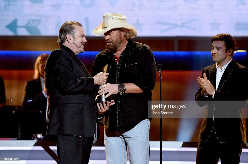 Singer-songwriter Toby Keith (R) presents singer-songwriter Jimmy Webb with an award onstage during the 10th Annual ACM Honors at the Ryman Auditorium on August 30, 2016 in Nashville, Tennessee.