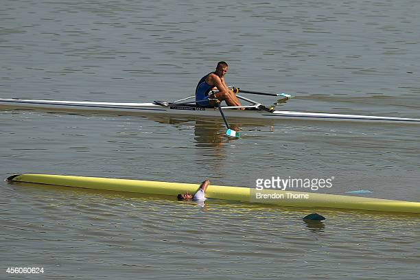 Singh Sawarn of India falls from his scull as Artyom Kudryashov of Uzbekistan looks on in the distance following the Men's Single Sculls during day...