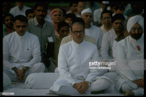 Singh , solemn-faced & sitting cross-legged, paying his respects at Mahatma Gandhi's tomb, honoring his bday.
