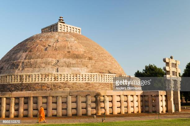 singhalese monk walking in front of sanchi stupa, a 2200 year old buddhist monument built by emperor ashoka in sanchi, madhya pradesh, india - stupa stock pictures, royalty-free photos & images