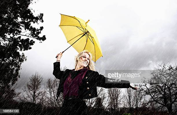 Singing and dancing in the rain: pretty woman enjoying thunderstorm