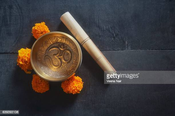 Singing Bowl/ Rin Gong with Om and marigold flowers on a wooden table