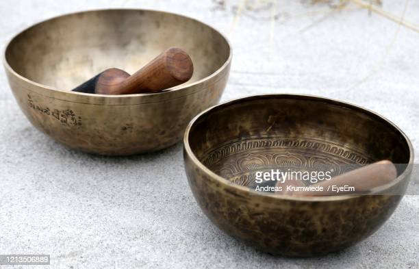 singing bowl with mallet at the beach - rin gong stock pictures, royalty-free photos & images