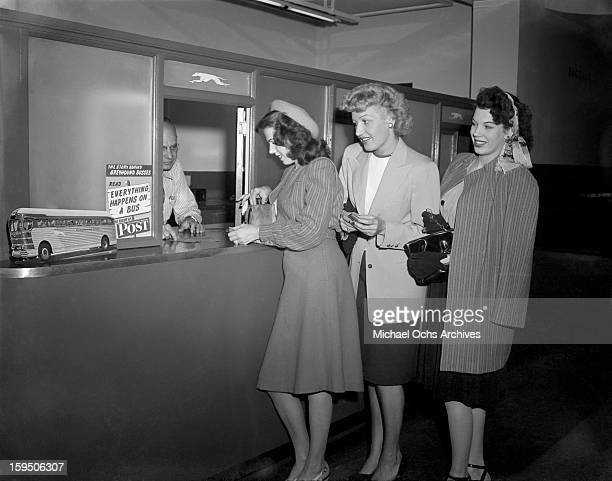 Singing group The Dinning Sisters pose for a purchase their tickets for Reno at the Greyhound Bus Terminal in Hollywood on March 23 1946 in Los...