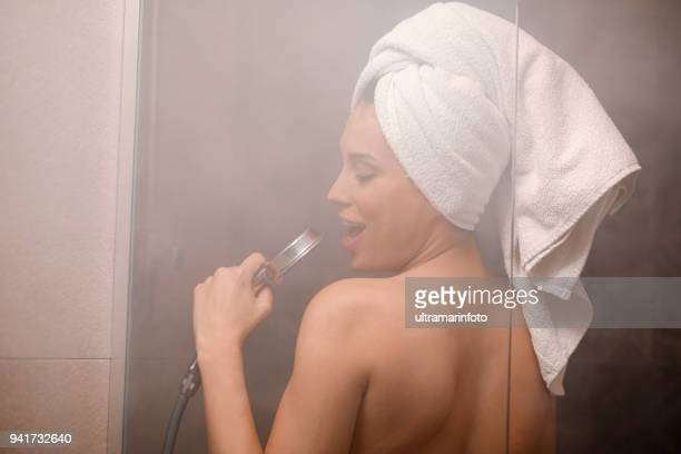 singing in the shower. natural beauty portrait beautiful young woman with a towel wrapped around her hair, after showering. in the bathroom. - cantare foto e immagini stock