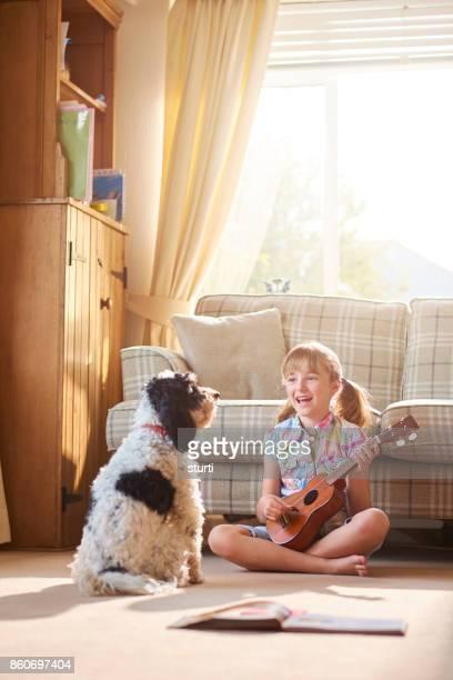 singing to her pet dog - ukulele stock pictures, royalty-free photos & images