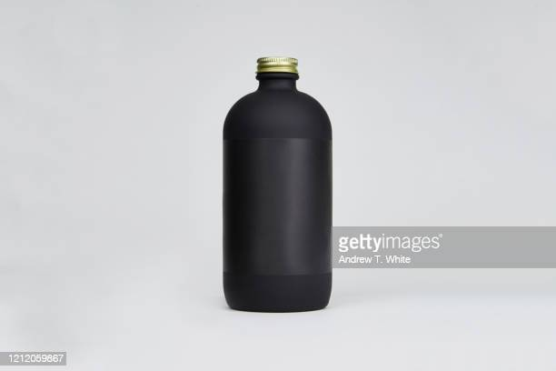 single 16 ounce matte black bottle with black label and gold tops on gray background - 商品 ストックフォトと画像