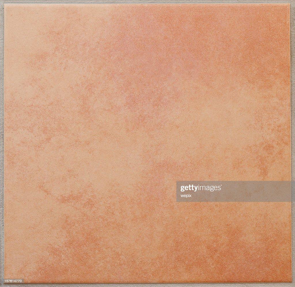 Single apricot colored ceramic tile textured full frame : Stock Photo