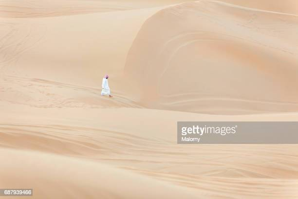 A single Arabian man walking barefoot through the desert