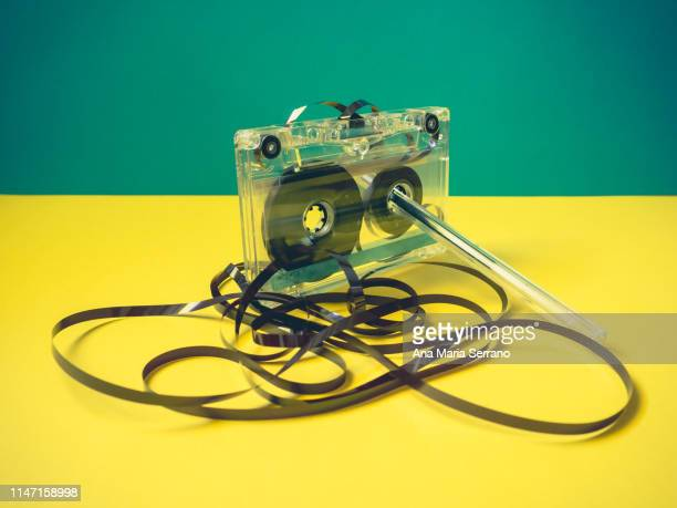 single audio cassette tape with loose tape spilling from top cassette and a pen on vintage style - ricordi foto e immagini stock