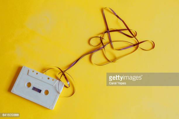 Single audio cassette tape with loose tape spilling from top cassette.