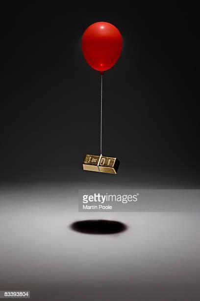 single balloon lifting gold bar