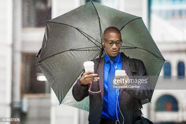 Einzelne schwarze Geschäftsmann arbeiten mit Telefon unter Dach bei Starkregen