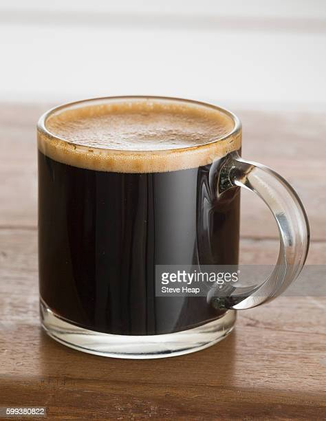 Single black expresso coffee in small glass cup or tankard with chocolate colored froth and standing on an old wooden table