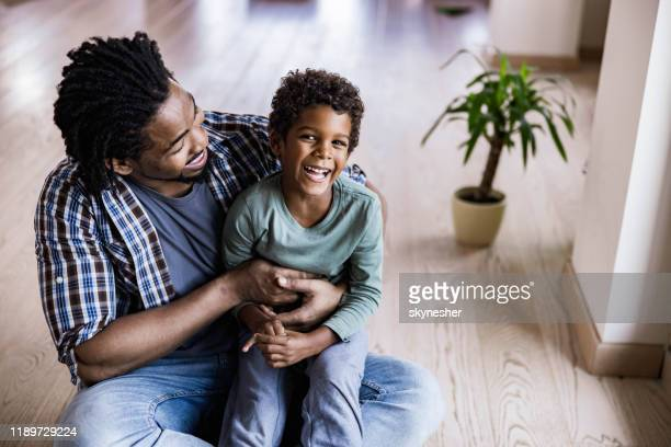 single black father having fun with his small boy at home. - affectionate stock pictures, royalty-free photos & images