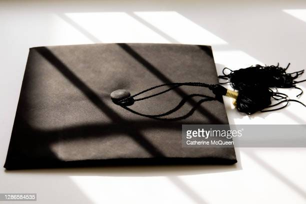 single black graduate cap on white background with shadow detail - certificate stock pictures, royalty-free photos & images