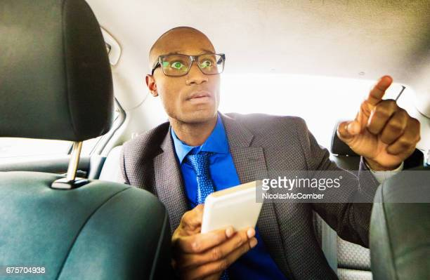 Single black male back seat driver with mobile phone