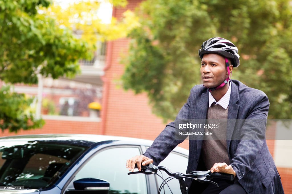 Single black male in his 30s cycling past car with helmet : Stock Photo