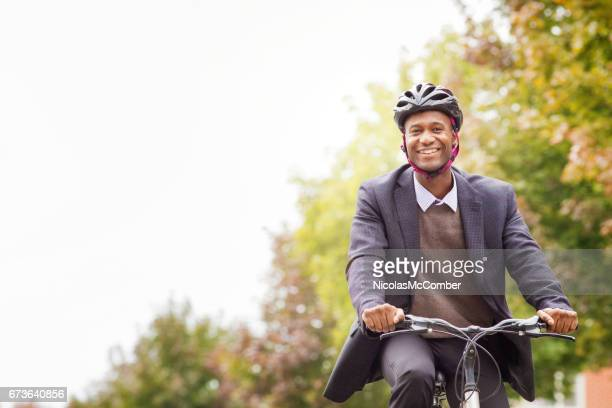 Single black male in his 30s smiling as he cycles to work