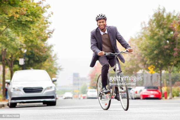 single black male in his 30s smiling while commuting to work by bicycle - bicycle stock pictures, royalty-free photos & images