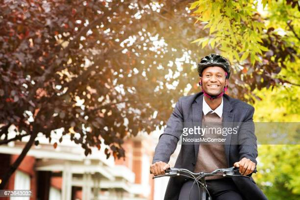 single black male in his 30s smiling while he bikes in residential area - black alley stock photos and pictures