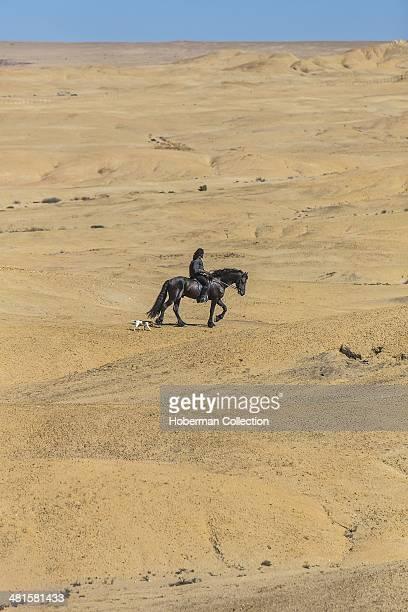 Single Black Male Riding A Black Horse At Swakopmund In Namibia