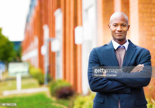 Single black man in suit smiling portrait with real estate background