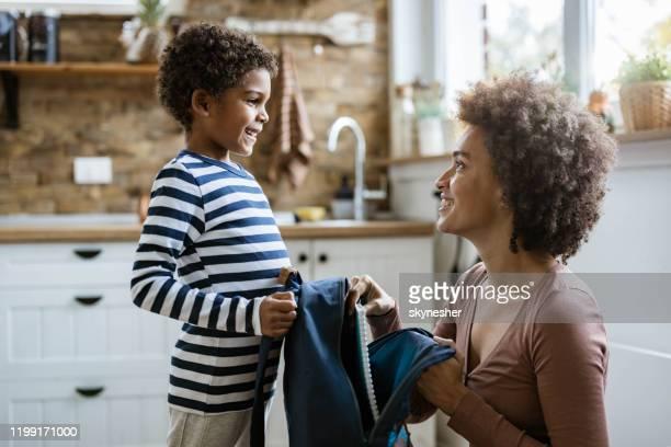 madre nera single che impacchetta il suo piccolo figlio per la scuola. - zaino da montagna foto e immagini stock