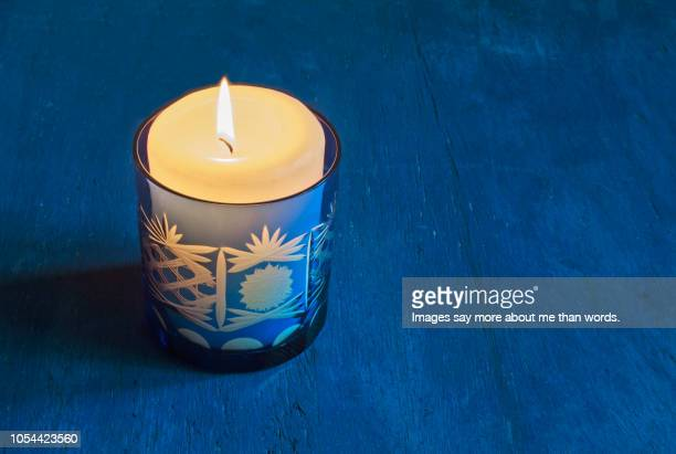 a single blue candleholder with a lit candle over a blue background. still life. - candle of hope stock pictures, royalty-free photos & images