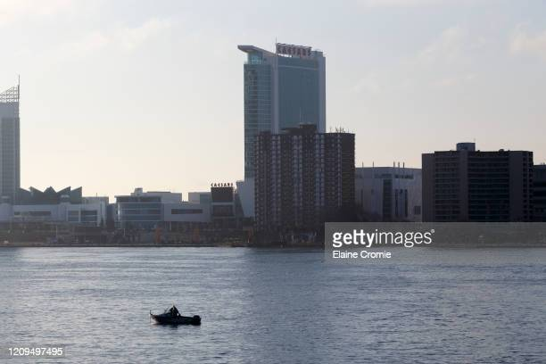 Single boat on the Detroit River across from Windsor, Ontario, Canada on April 8, 2020 in Detroit, Michigan. In an effort to slow the spread of the...