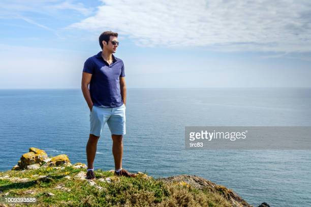 retrato de estilo de vida único homem brasileiro no promontório de praia - calção - fotografias e filmes do acervo