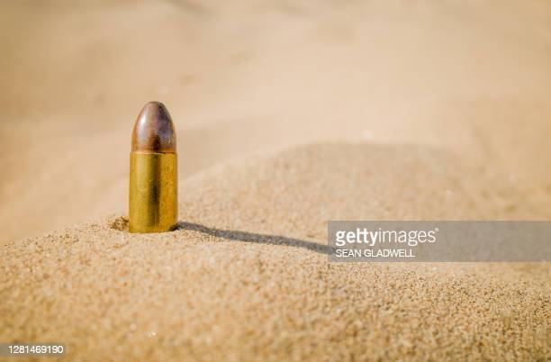 single bullet on sand - gun control stock pictures, royalty-free photos & images