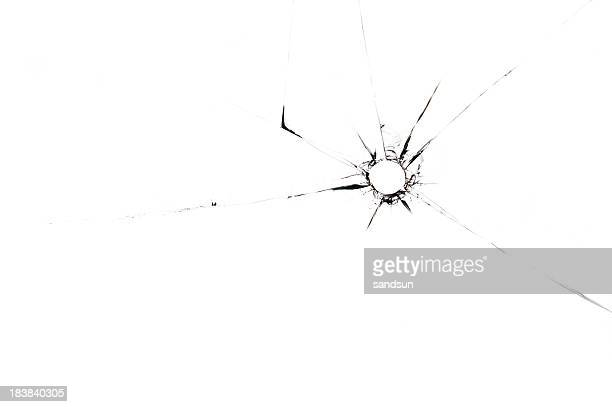A single bullet whole through glass on a white background