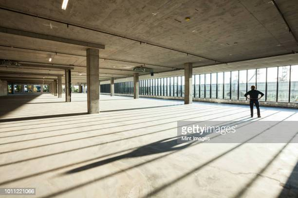 single businessman exploring new empty raw business space for a new office, light streaming in large windows. - calm before the storm stock pictures, royalty-free photos & images