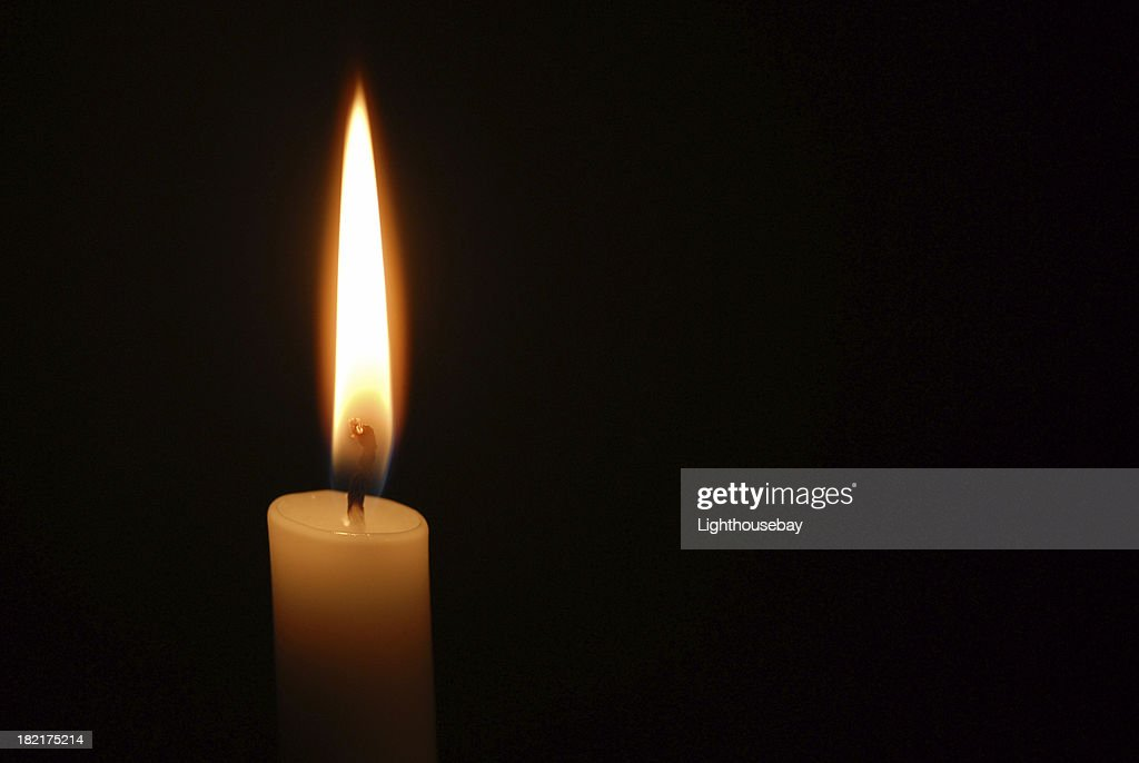 Single candle flame on horizontal black background : Stock Photo