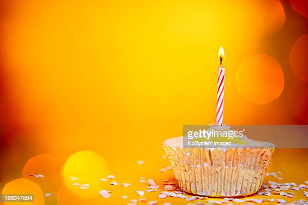 Single candle on a cupcake with orange background