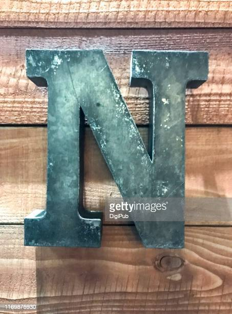 single capital letter 'n' on plank wall - letter n stock pictures, royalty-free photos & images