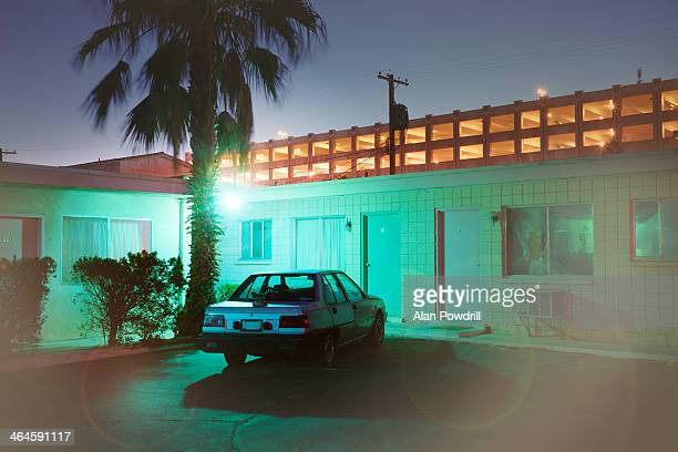 single car at back of blue motel at night - motel stock photos and pictures